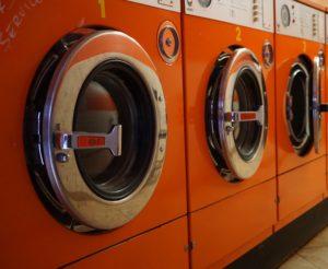 コインランドリーの洗濯機が並ぶ画像