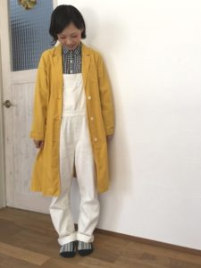 イエロースプリングコートとサロペットを着用した女性の画像