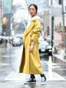 白パーカーにイエロースプリングコートを着用した女性の画像