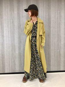 花柄ワンピにイエロー系のスプリングコートを着用した女性の画像