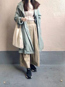 ナチュラルなコーデにグリーンのスプリングコートを合わせた女性の画像