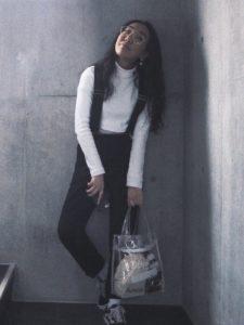 白のトップスにサスペンダーを着用した女性の画像