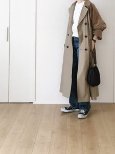 袖と身頃のカラーが少し違うトレンチコートをコーディネートした女性の画像