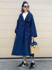 ボリュームのあるネイビースプリングコートを着用した女性の画像