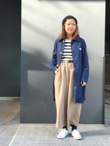 ボーダーTとワイドパンツにネイビースプリングコートを着用した女性の画像