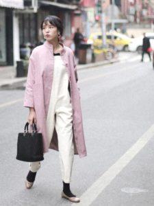 白のサロペットにピンクスプリングコートを着用した女性の画像