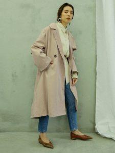 シャツとデニムにピンクスプリングコートを着用した女性の画像