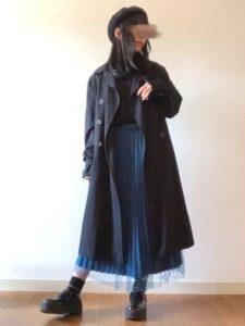 ブループリーツスカートに黒スプリングコートを着用した女性の画像