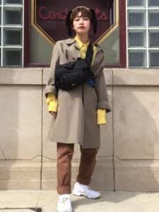 イエローシャツとブラウンパンツにベージュスプリングコートを着用した女性の画像