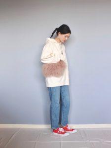 トレーナーとデニムに赤いスニーカーをコーディネートした女性の画像