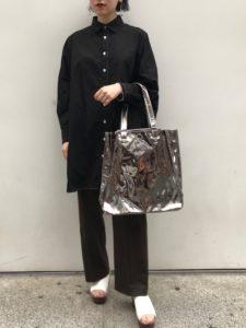 黒シャツとブラウンボトムで同系色のコーディネートをした女性の画像